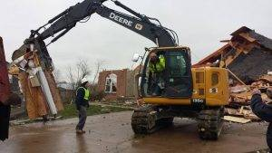 Disaster response volunteers use a backhoe