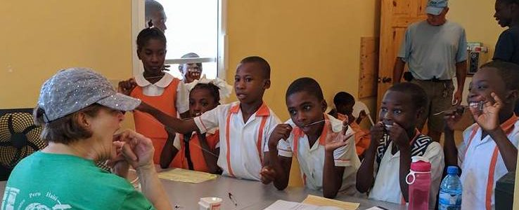 Volunteer on a mission trip teaches kids oral hygiene