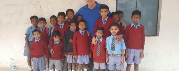 India mission trip volunteer stands with schoolchildren