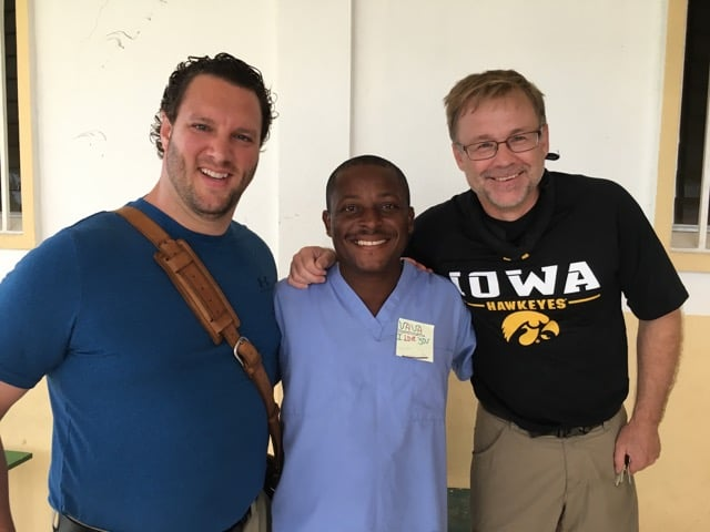 A group of three dentists on a dental mission trip embrace