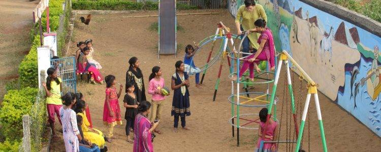 Women and girls gather in a playground in India
