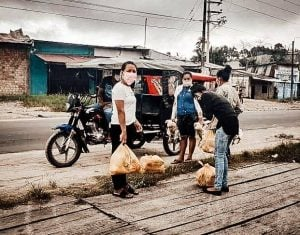 Four people wearing masks unload grocery bags of food from Peru missionaries