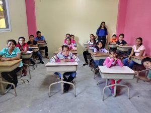 A classroom with Guatemalan children at four rows of desks
