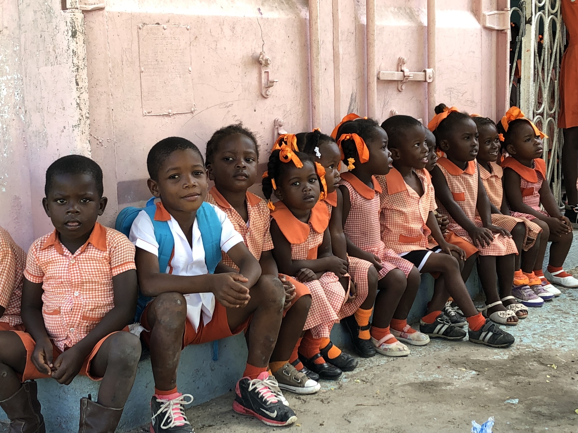 12 Guatemalan children sit against an orange wall outside of their school