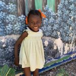A young girl smiles after she receives child sponsorship benefits