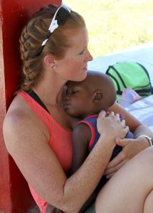 Mission Trip ambassador holds a small boy when visiting with sponsor-a-child program